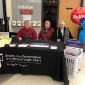 Smiling people sitting behind a donation table