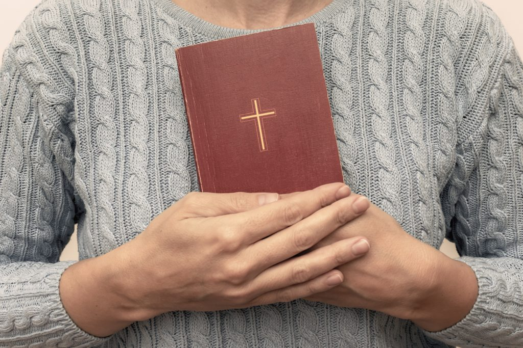 Young praying christian woman's hands holding holy bible with a cross on a cover