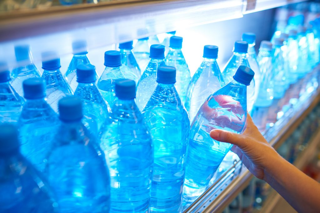 Crop customer taking bottle of water from shelf while shopping in supermarket