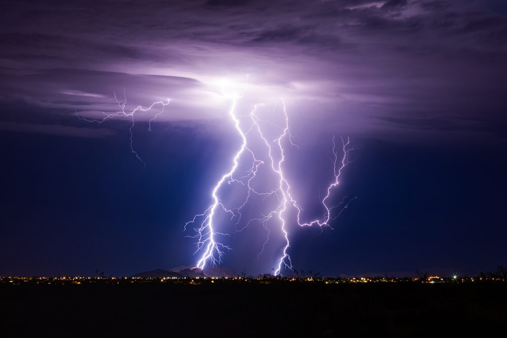 Lightning bolt storm with thunderstorm clouds at night.